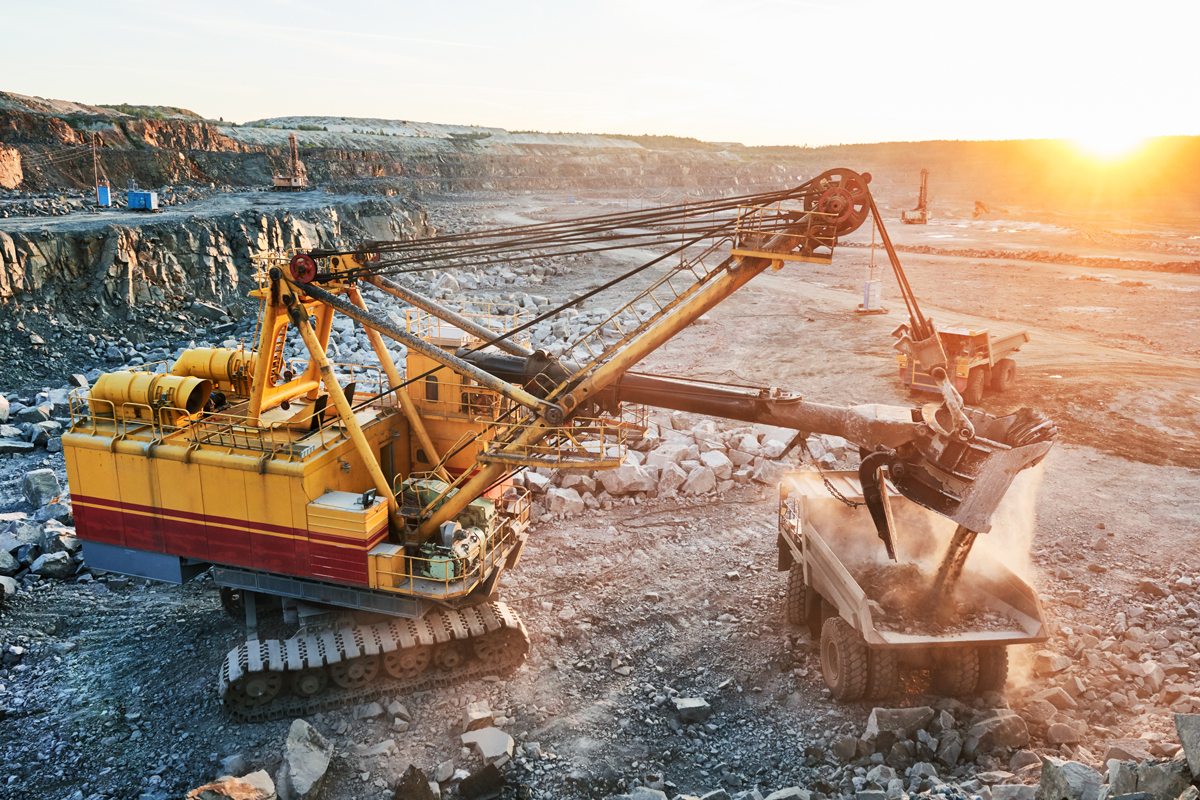 Photo of mining equipment with sun setting in the background.