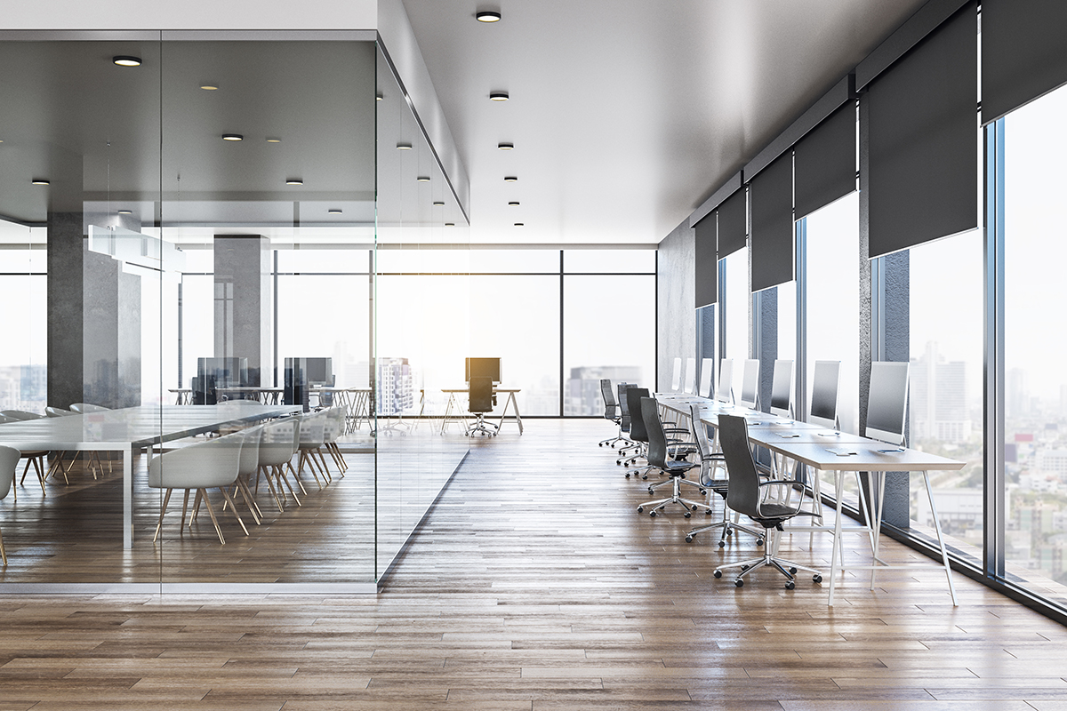 Empty office with windows overlooking a city.