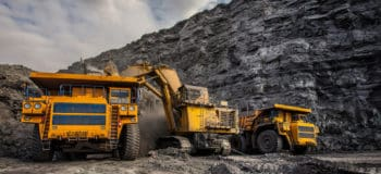 Three large mining machines parked on the edge of a gravel pit.