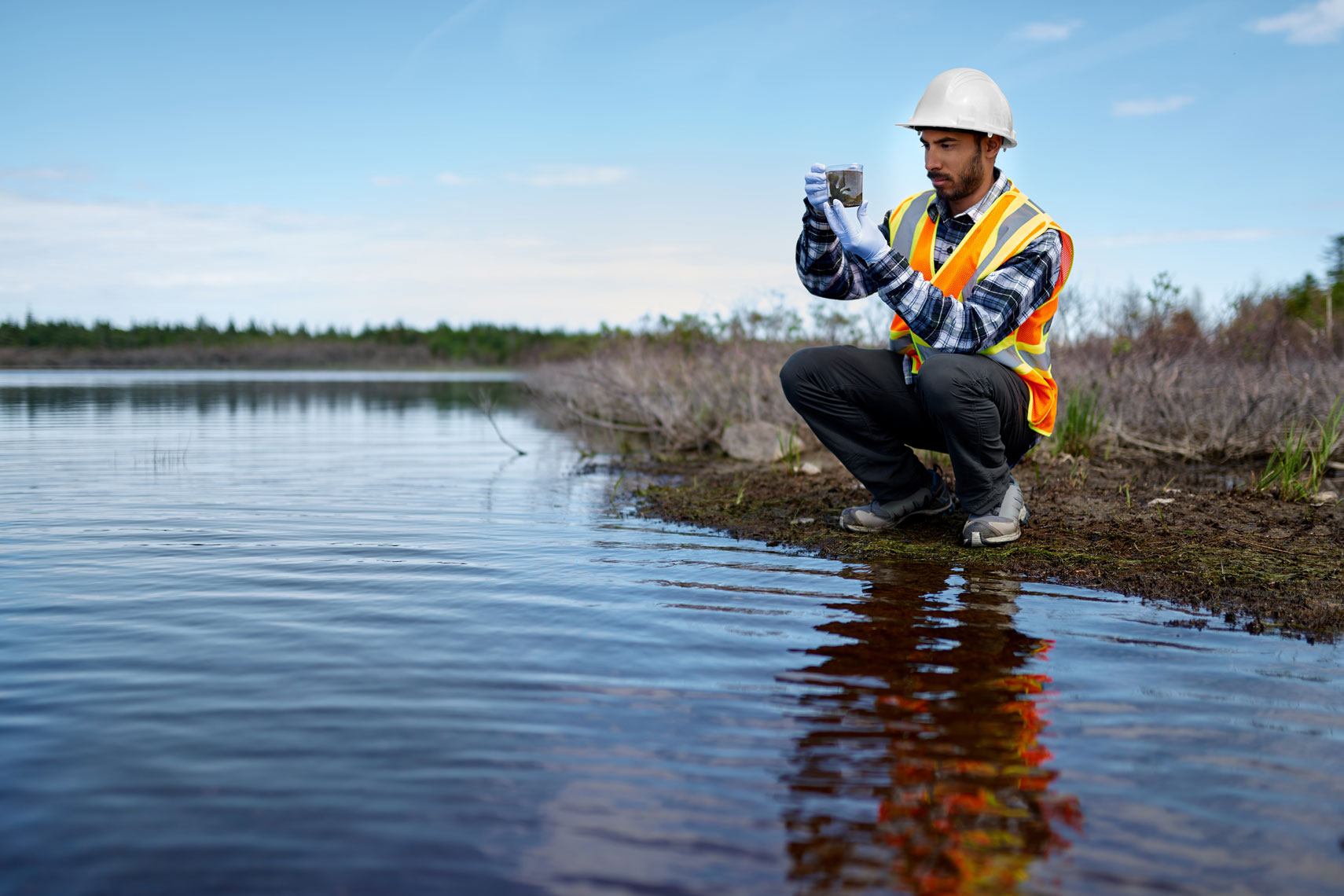 Marine biologist crouches at edge of river analysing water test results and algea samples