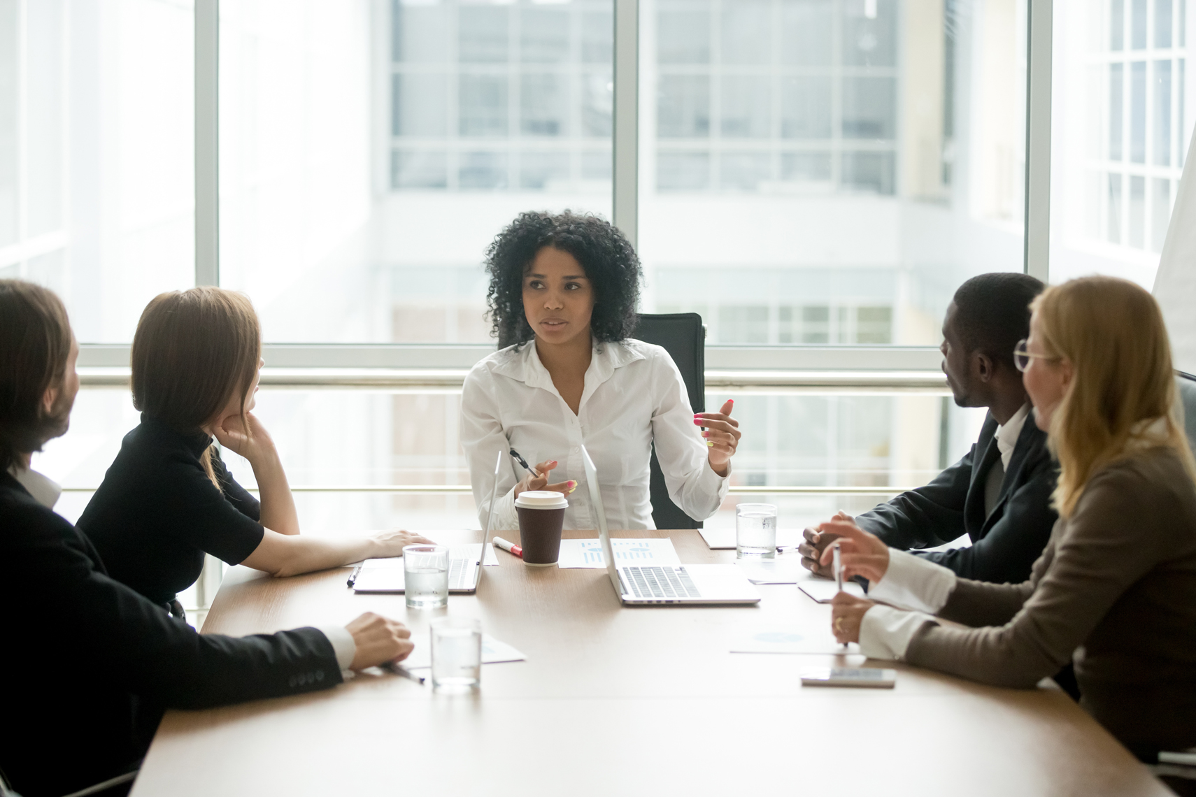 Multiracial business people talking, sitting at office boardroom table.